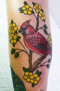 red cardinal bird tattoo with yellow flowers
